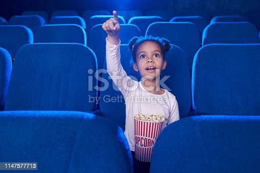istock Cute girl poiniting with finger at screen in cinema. 1147577713