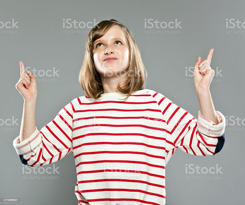 Cute girl pointing Portrait of cute girl wearing striped blouse and jeans, standing against grey background and pointing with index fingers, looking up. 10-11 Years Stock Photo