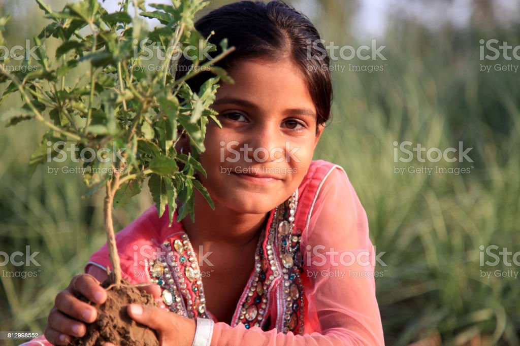 Cute girl portrait in the nature holding plant stock photo