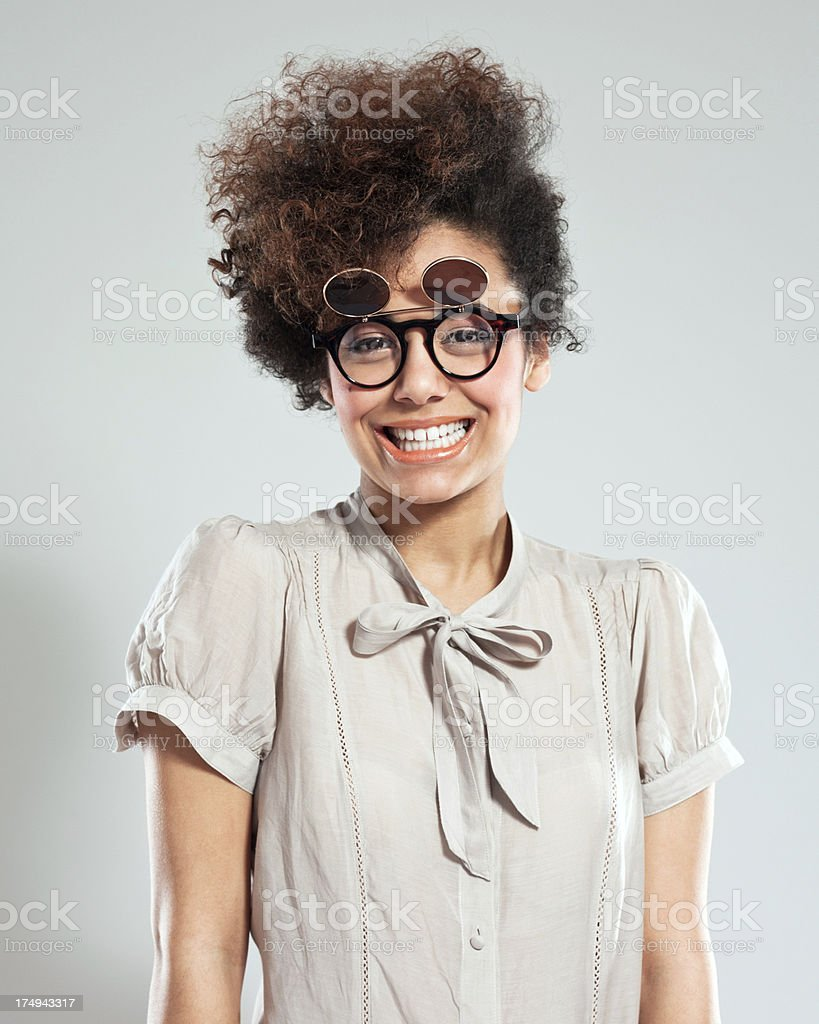 Cute Girl Portrait Portrait of teenaged afro girl wearing funny glasses and smiling at camera. Studio shot, grey background. 18-19 Years Stock Photo
