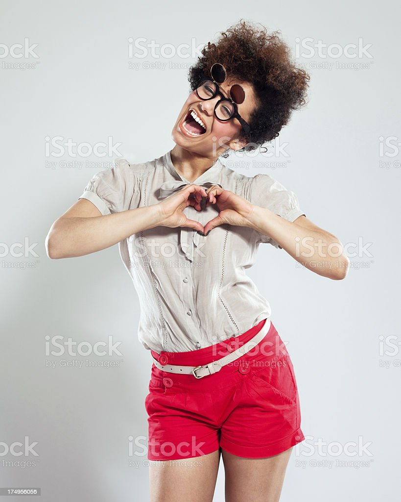 Cute Girl Portrait Portrait of teenaged afro girl wearing funny glasses and showing heart shape with hands. Studio shot, grey background. 18-19 Years Stock Photo