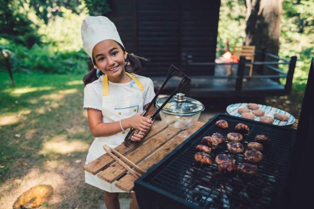 niedliche mädchen vorbereitung grill im garten - kindergrill stock-fotos und bilder