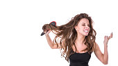 cute girl pulls out a comb from tangled hair on a white background. Hair health concept