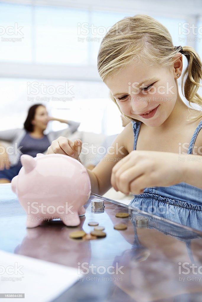 Cute girl putting money in piggy bank stock photo