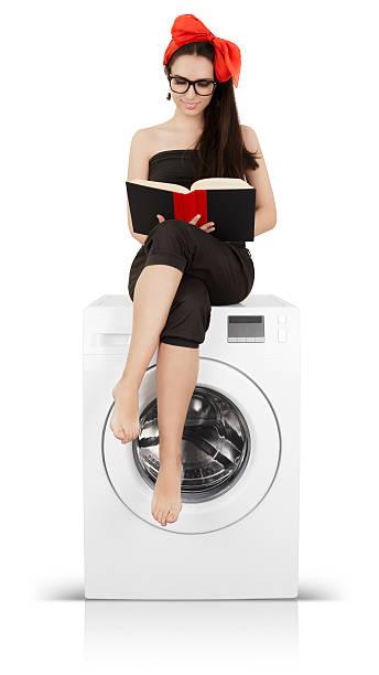 hübsche mädchen liest ein buch auf eine waschmaschine - leise waschmaschine stock-fotos und bilder