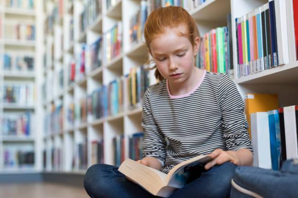 schattig meisje leesboek in bibliotheek - a little girl reading a book stockfoto's en -beelden