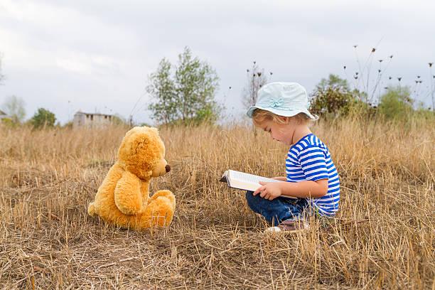 hübsche mädchen liest ein buch teddy - geschichten für kinder stock-fotos und bilder