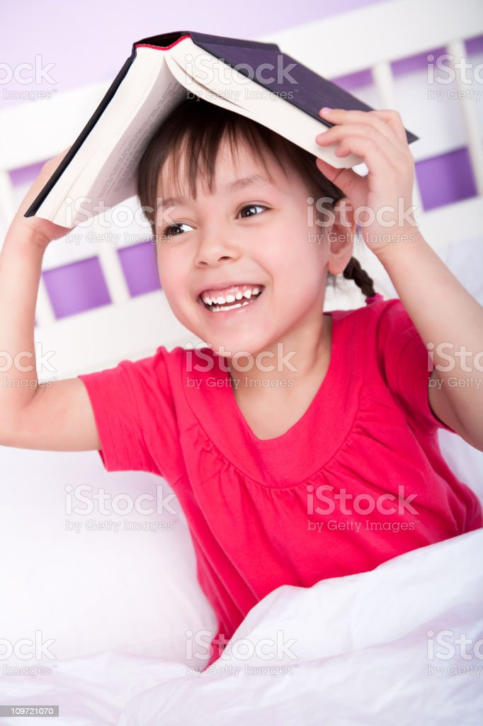 Cute girl reading in bedroom royalty-free stock photo
