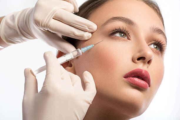 cute girl receiving hyaluronic acid treatment - injection de toxine botulique photos et images de collection