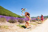 Exited preteen girl running with rainbow kite through lavender meadow