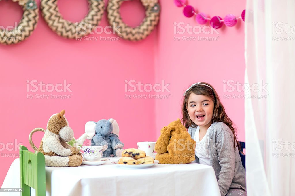 Cute girl sharing a tea party with her stuffed animals stock photo