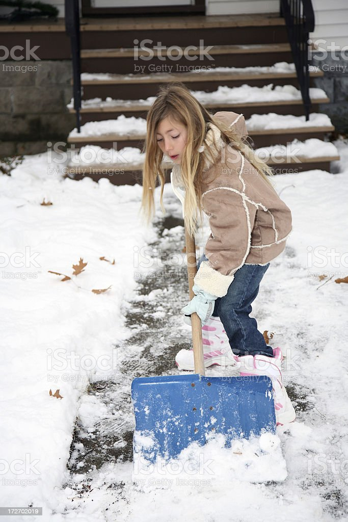 Cute girl shoveling snow after blizzard royalty-free stock photo