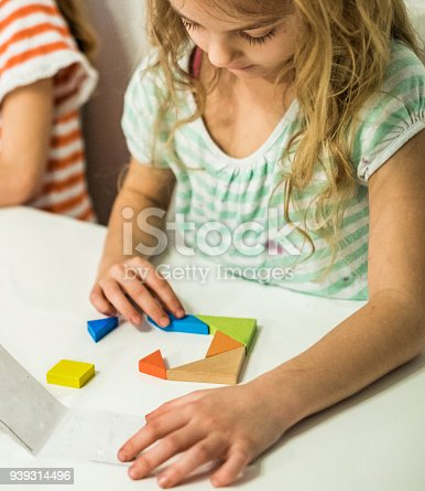 istock cute girl sitting at the table solving puzzle 939314496