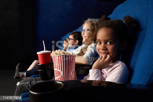istock Cute girl sitting in cinema with friends, looking at camera. 1147577624