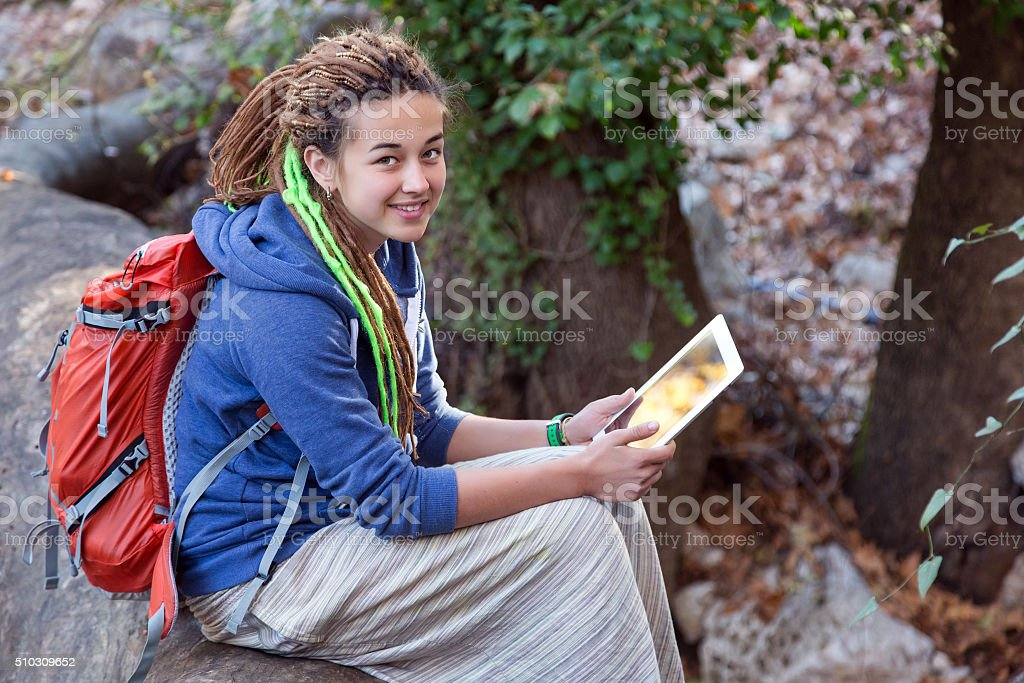 Cute Girl sitting in Forest smiling and holding white Tablet stock photo
