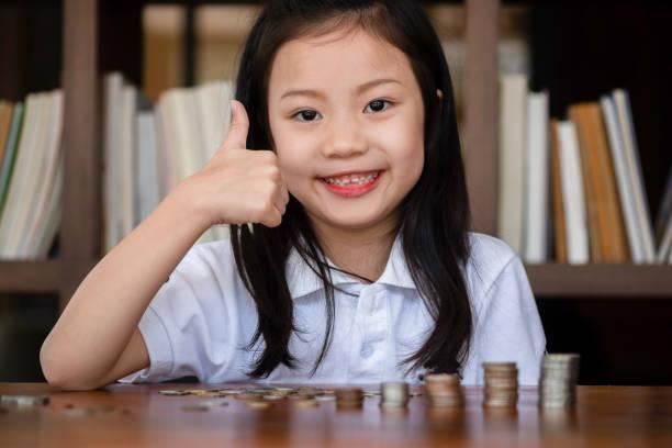 süße Mädchen in der Bibliothek setzen Geldmünze auf dem Tisch stapeln, Geld-Konzept sparen – Foto