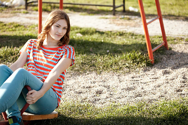 cute girl sitting in park stock photo