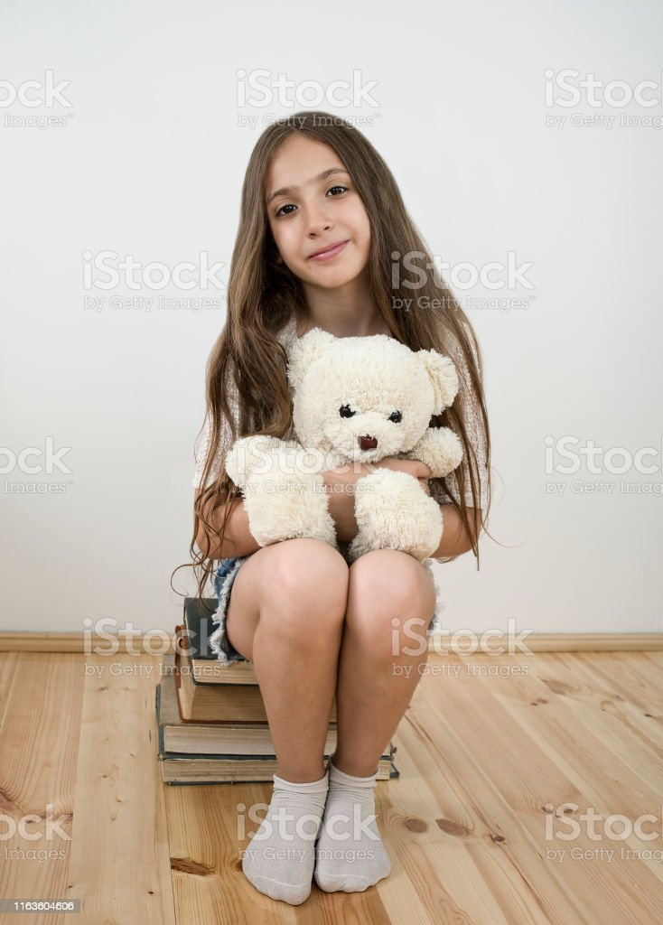 portrait of cute girl sitting on a pile of books and holding teddy...