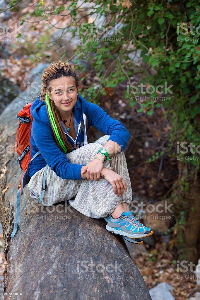 Cute Girl sitting on fallen Tree Stalk in wild Forest stock photo