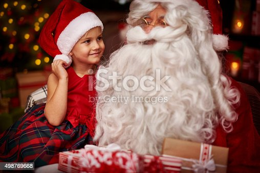 istock Cute girl sitting on the santa's knees 498769668