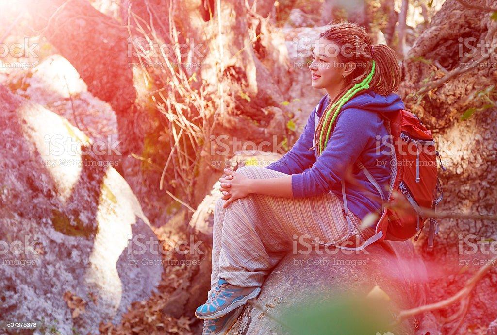 Cute Girl sitting on Tree Stalk Forest enjoying warm Sunshine stock photo