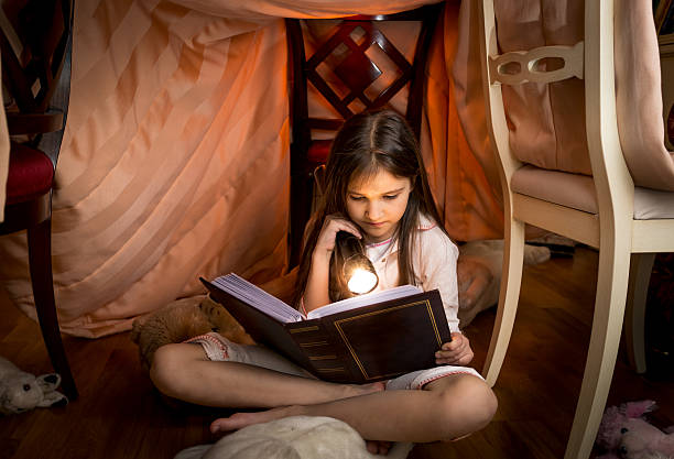cute girl sitting under blanket and reading a book - fort stockfoto's en -beelden