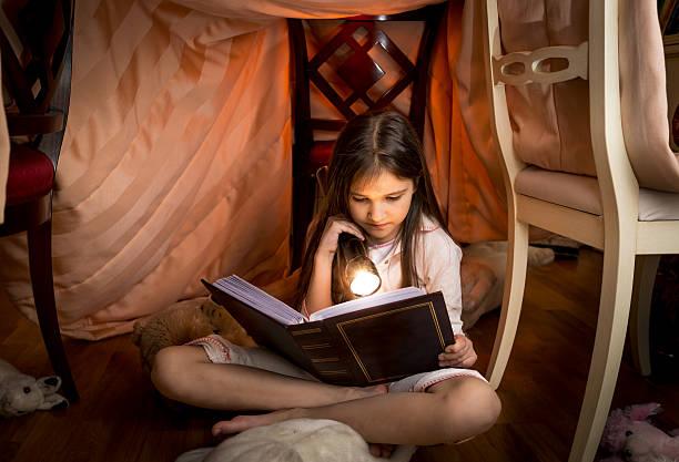 cute girl sitting under blanket and reading a book - fort bildbanksfoton och bilder