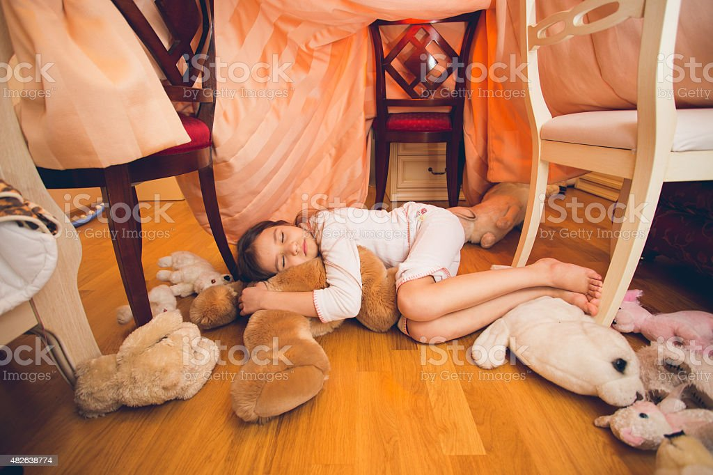 cute girl sleeping on floor with toys at bedroom stock photo