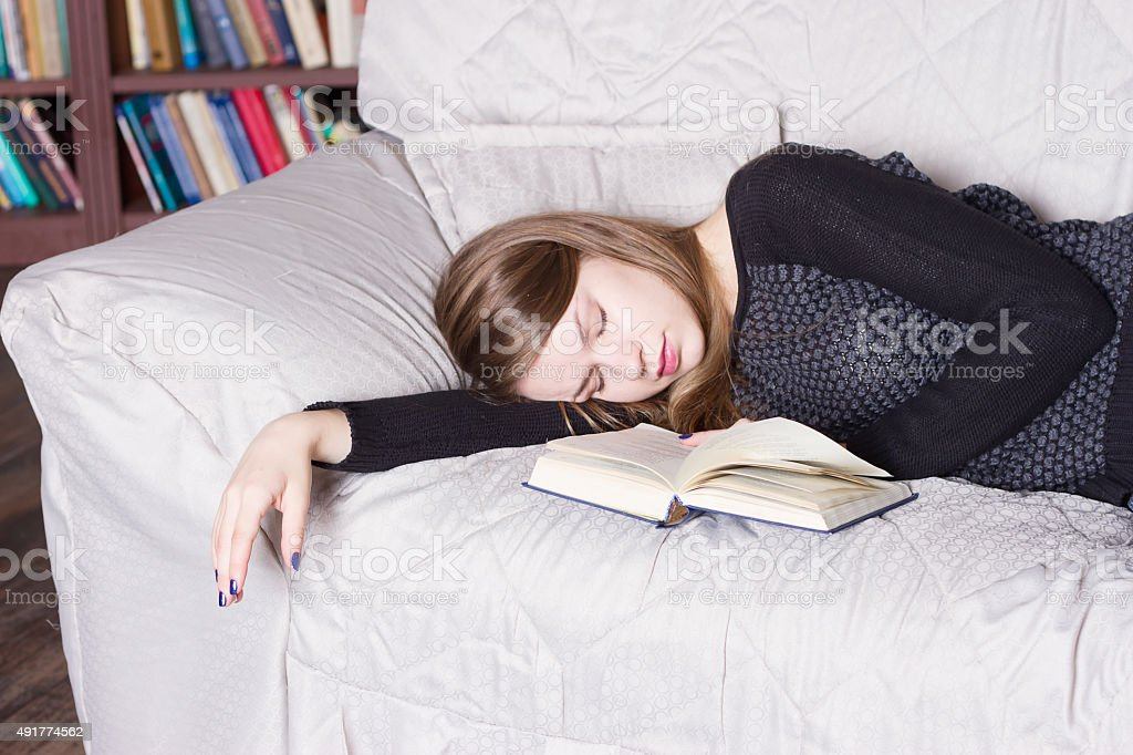 Cute girl sleeping while holding a book lying stock photo
