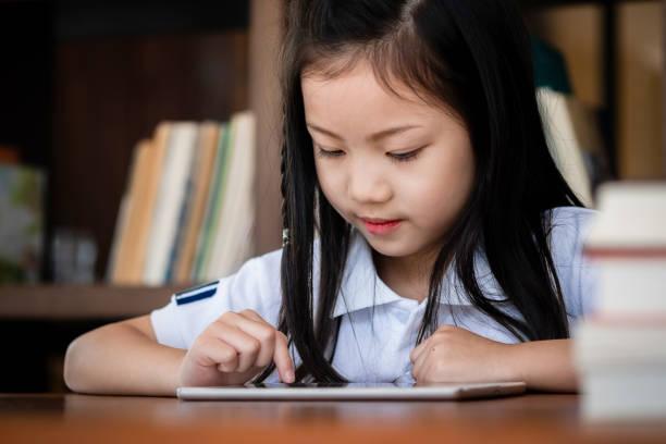süße Mädchen Lächeln sitzen und spielen Laptop-Computer in der Bibliothek, Kinder-Konzept, Bildungskonzept – Foto