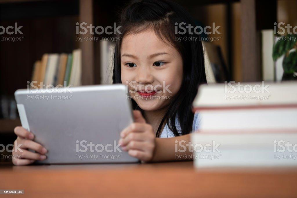 niedliche Mädchen Lächeln Sitdown und spielen Tablet-Smartphone in der Bibliothek, Kinder-Begriff, Bildung – Foto