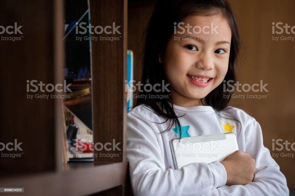 niedliche Mädchen Lächeln stehen und halten Tablet-Smartphone in der Bibliothek, Kinder-Begriff, Bildung – Foto
