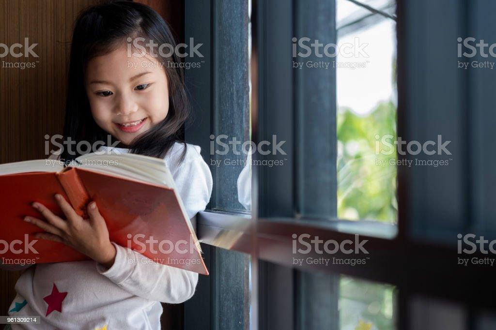 niedliche Mädchen lächelte und Stand zu lesen Buch in der Bibliothek, Kinder-Begriff, Bildung – Foto