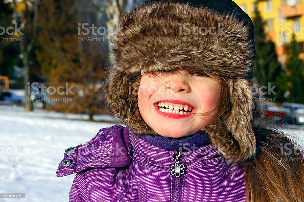 Cute girl smiling in snow with fur hat, sunny winter stock photo