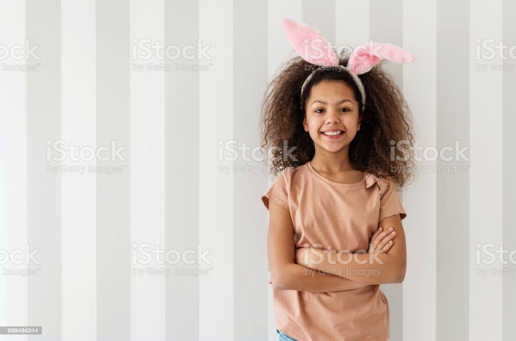 Niedliche Mädchen lächelnd über eine gestreifte Wand mit Hasenohren – Foto