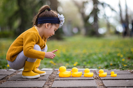 Girl crouching in her yellow boots near a family of yellow toy ducks