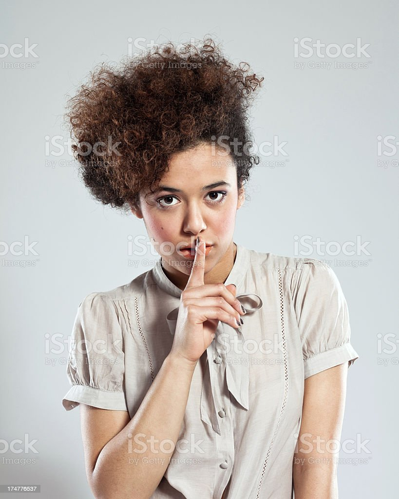 Cute Girl sushing Portrait of cute teenaged afro girl puts a finger to her lips, gesturing for quiet, looking at camera. Studio shot. 18-19 Years Stock Photo