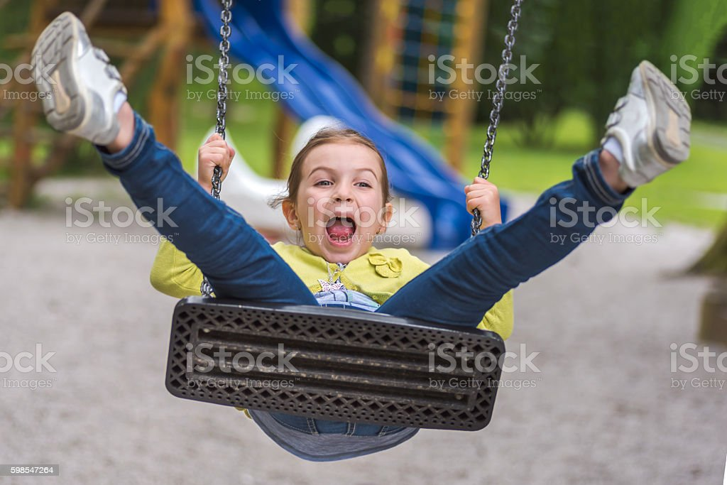 Cute Girl Swing on Playground Acting Silly stock photo
