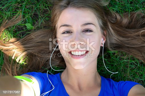 Beautiful fitness girl taking a selfie photo while resting after outdoors workout.
