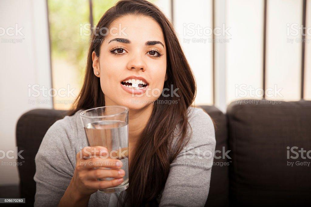 Cute girl taking an aspirin stock photo