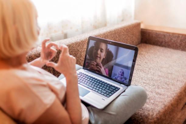 urocza dziewczyna rozmawia z babcią w czacie wideo na laptopie, życie w czasie kwarantanny - dojrzały zdjęcia i obrazy z banku zdjęć
