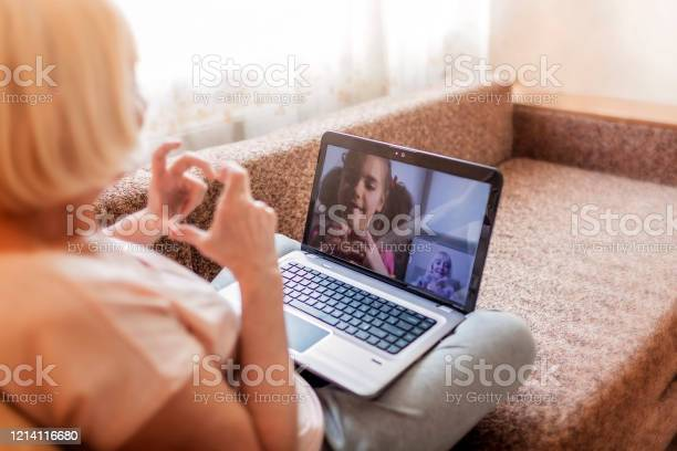 Cute girl talking with her grandmother within video chat on laptop, life in quarantine time Cute girl talking with her grandmother within video chat on laptop, digital conversation, life in quarantine time, self-isolation Adult Stock Photo
