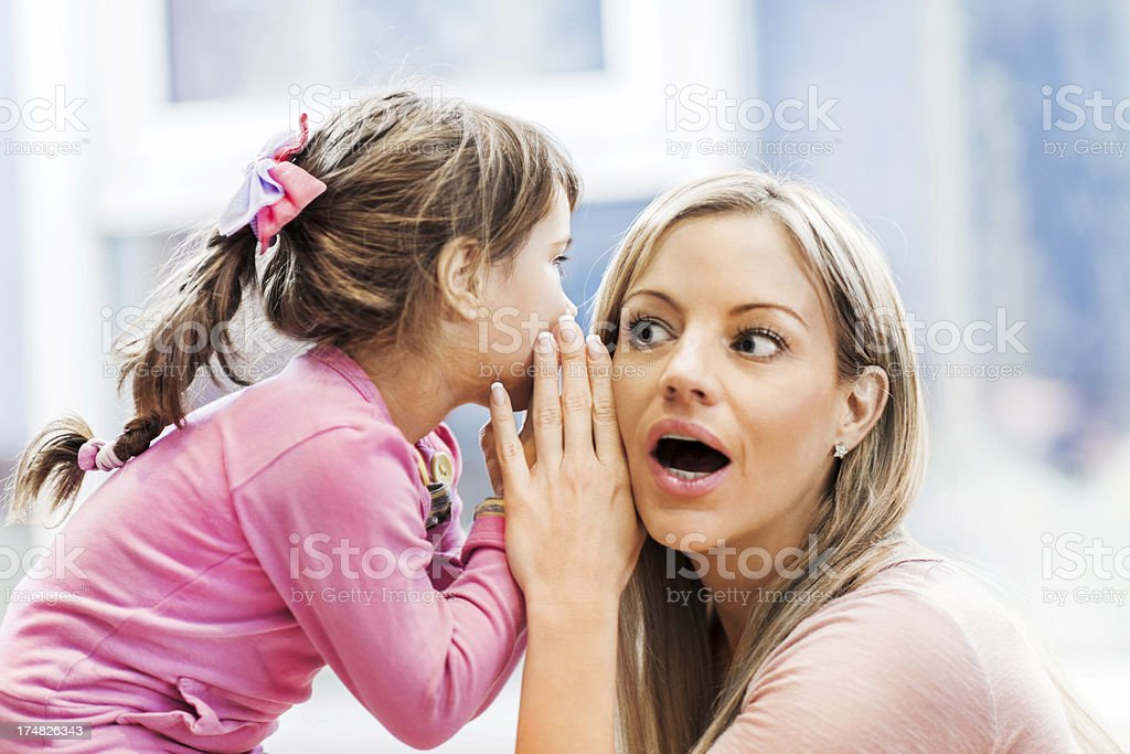 Cute girl telling a secret to her mother stock photo