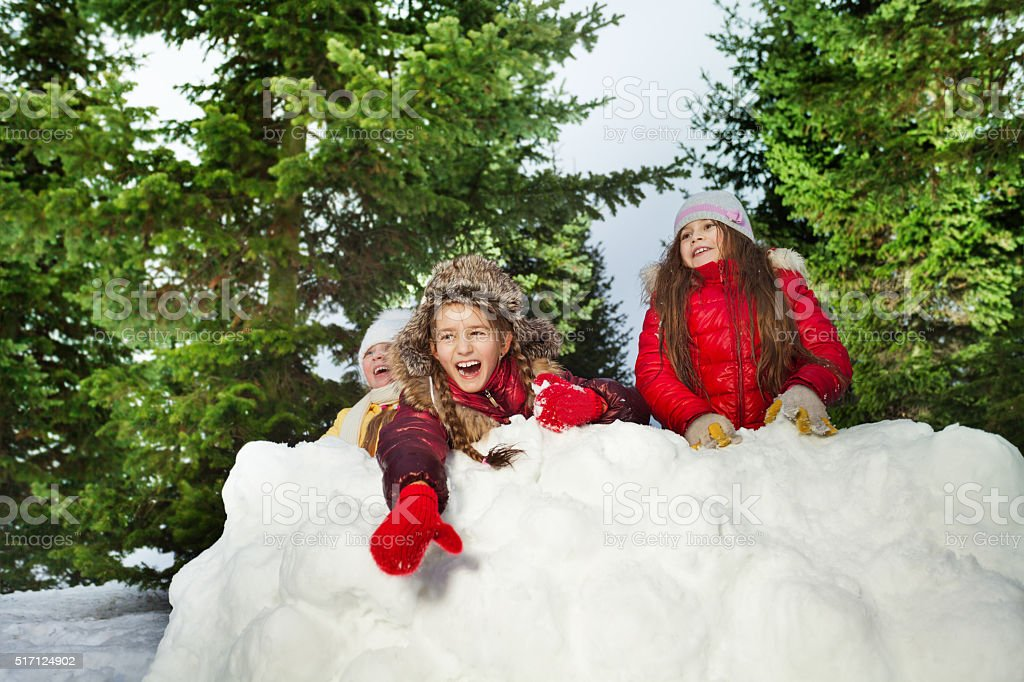 Cute girl throwing snowballs playing with friends stock photo
