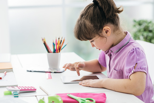 Cute girl using a digital tablet and doing her homework, technology and back to school concept