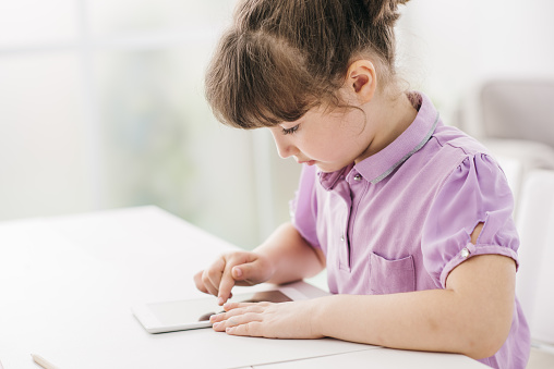 Cute girl using a digital tablet and doing her homework, education and technology concept