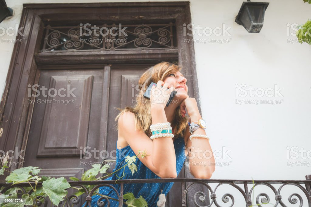 Cute girl using cellphone in front of a old house. royalty-free stock photo