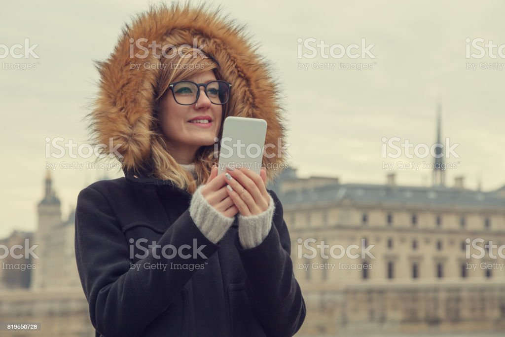 Cute girl using cellphone in Paris, France. stock photo