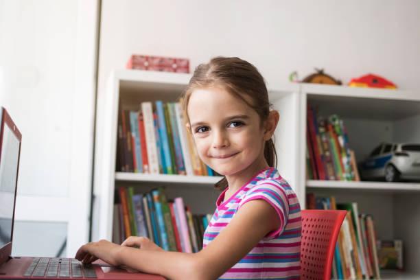 Jolie fille à l'aide d'ordinateur portable. Jeu vidéo. Faire ses devoirs. Portrait - Photo