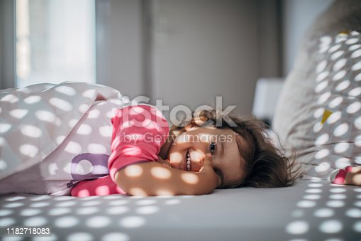 Cute little girl waking up in bed